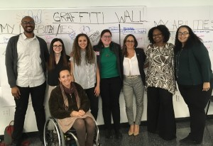 Debbie Fink with presenters and facilitators at training for Female College Students with Disabilities in front of a graffiti wall smiling together