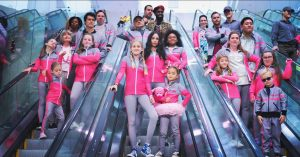 The cast of Feel The Beat on Netflix riding down three separate escalators