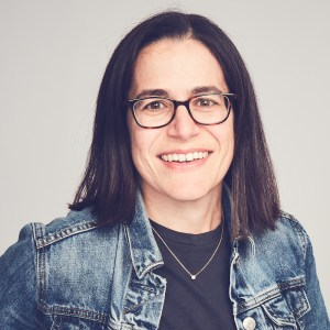 Carolyn Lertzman smiling headshot. Lertzman is a white woman with black hair down to her shoulders, wearing glasses, a necklace and a denim jacket.