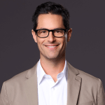 David Schulner smiling headshot. Schulner is a white man with short black hair, is wearing glasses and a tan suit