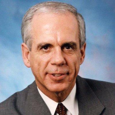 Hon. Tony Coelho headshot wearing a suit and tie. Coelho is a white man with short grey hair
