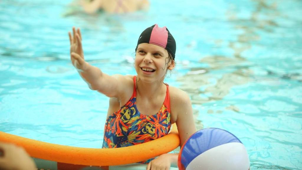 A young girl with a disability in a pool with one hand on the side of the pool and one arm up in the air.