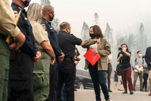 Kamala Harris bumps elbows with a firefighter in Auberry California. Nasreen Alkhateeb is in the background filming