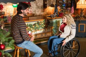 A scene from Christmas Ever After with Ali Stroker and Poster for Christmas Ever After on Lifetime with Ali Stroker and Daniel di Tomasso having a conversation