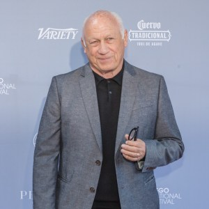 Joey Travolta smiling in front of a banner with the variety logo and Cuervo traditional logo on it