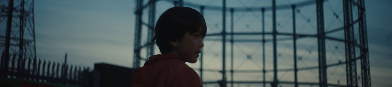 A young boy walking outside in a scene from The Reason I Jump