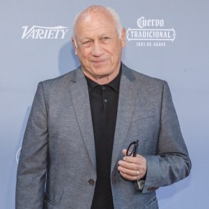 Joey Travolta wearing a suit smiling in front of a banner with the Variety logo on it