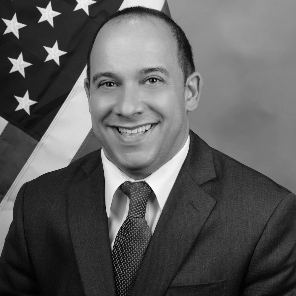Joseph Bensmihen headshot smiling in front of an American flag