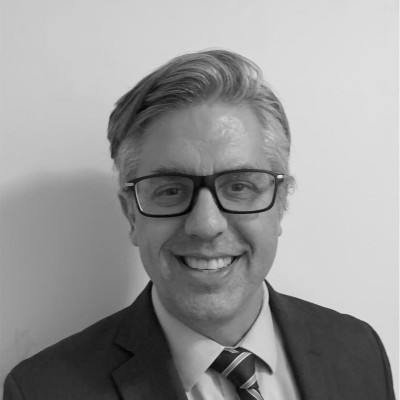 Craig Leen smiling headshot wearing glasses and a suit and tie