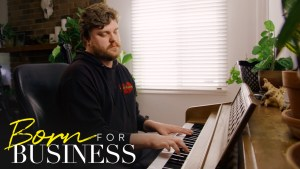 Chris playing piano in a scene from Born For Business. Show logo in bottom left.