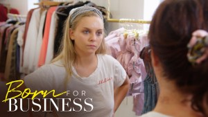 Lexi in a room with lots of clothing, looking at someone else. Born For Business logo in bottom left