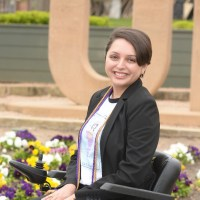 Alejandra Tristan smiling headshot. Tristan is seated in her wheelchair