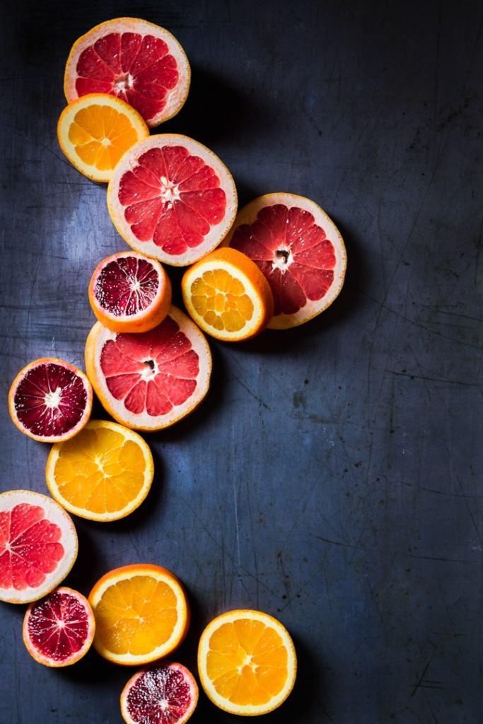 slices of winter citrus on dark background