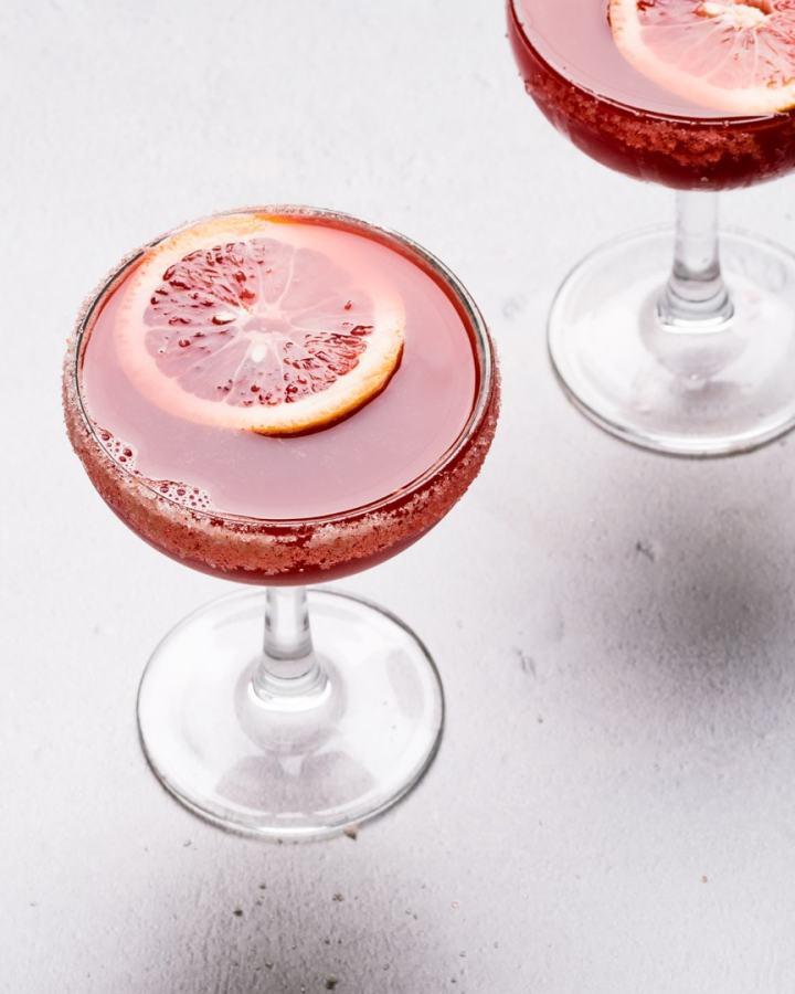 two coupe glasses filled with blood orange margaritas
