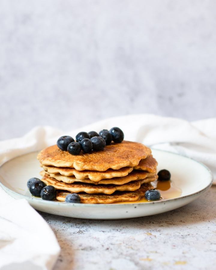 stack of blueberry gluten-free pancakes wih maple syrup on plate