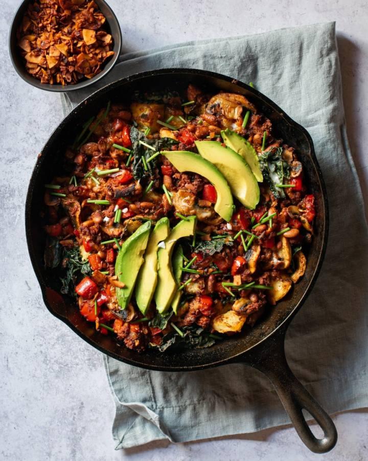 cast iron skillet with beans, soyrizo, vegan feta, avocado, bell pepper, coconut bacon
