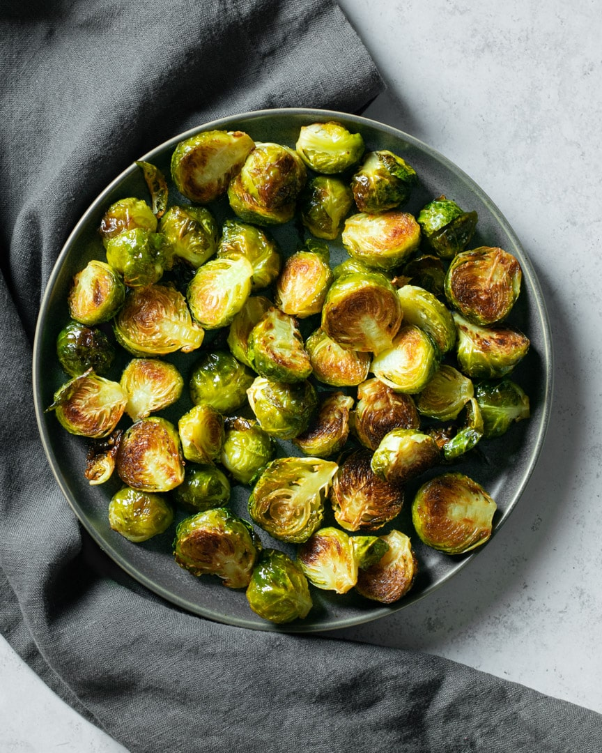 roasted brussels sprouts on grey p late with grey napkin