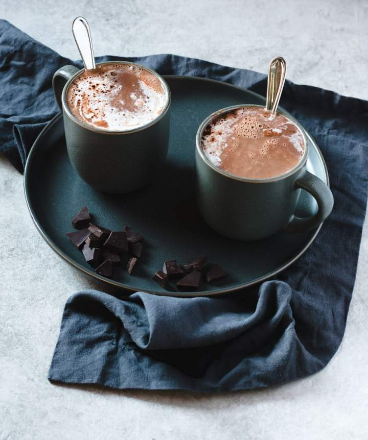 two mugs of hot cocoa on a dark plate with chopped chocolate