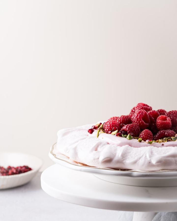 aquafaba pavlova with coconut cream, raspberries, pistachio