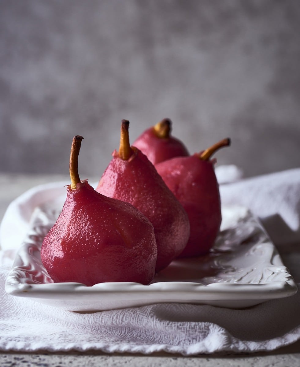 four red wine poached pears on white plate with grey background and white napkin