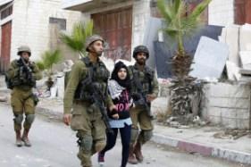 A Palestinian schoolgirl being arrested by Israeli soldiers. Photo: Muhesen Amren APA images