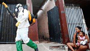 Health official walks past residents as he carries out fumigation to help control the spread of chikungunya and dengue fever, Mar.6, 2015 | Photo: Reuters