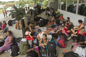 FILE - In this Nov. 16, 2015 file photo, Cuban migrants sit outside a Costa Rican immigration building on the border with Nicaragua, in Penas Blancas, Costa Rica, after Nicaragua closed its border to all Cuban migrants, leaving them stuck in Costa Rica. Costa Rica plans to raise the ongoing issue of 5,000 Cuban migrants stranded within its borders when Central America's leaders meet in El Salvador on Friday, Dec. 18. (AP Photo/Esteban Felix, File)