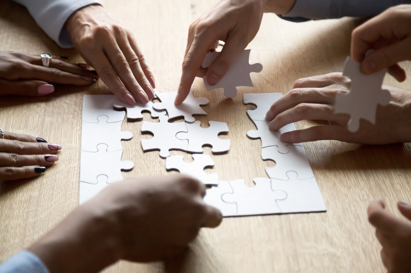 Multiple people assemble a jigsaw puzzle together
