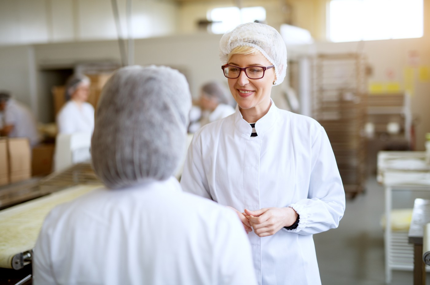 Two workers wearing hairnets and while coats stand in what looks like a factory. One has their back to the camera and is a bit shorter, The other is a white woman, she is smiling and looking into the face of the other worker. The background is blurred.