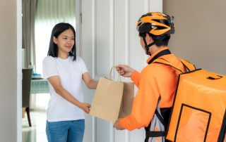 A delivery driver dressed in an orange shirt with matching bicycle helmet and wearing an insulated food delivery backpack style bag hands a brown paper bag to a woman.