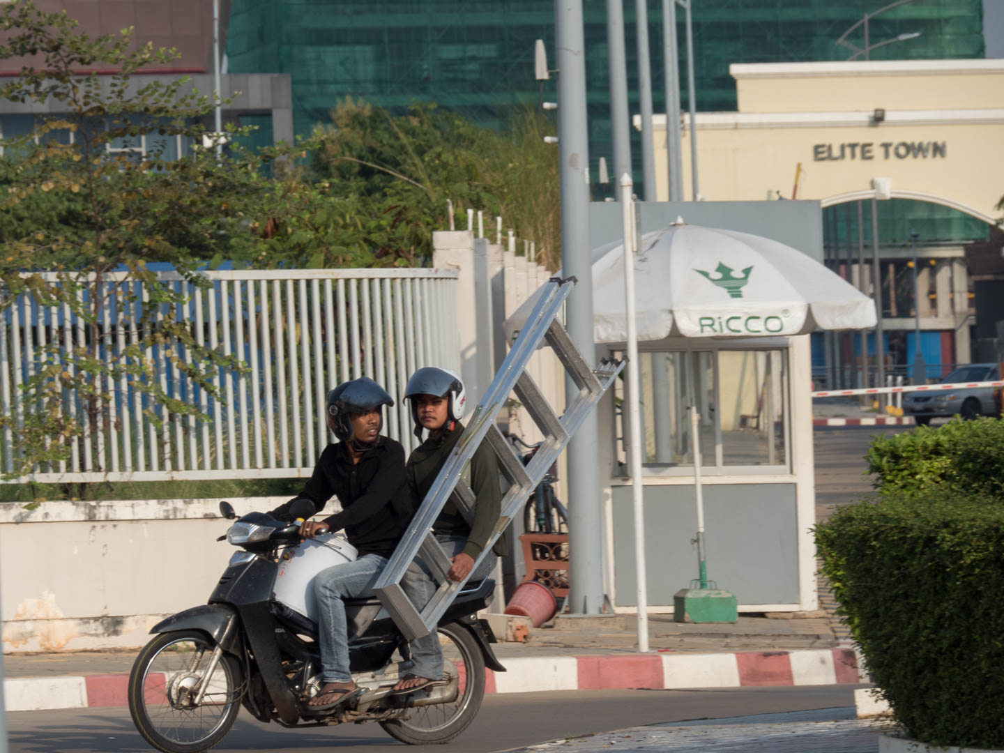 a moto carrying 2 men and a ladder