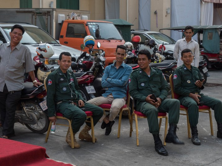 3 policemen and 3 men waiting outside a wedding