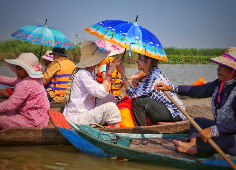 Two friends on a boat with umbrellas in Tonle Sap lake, Cambodia