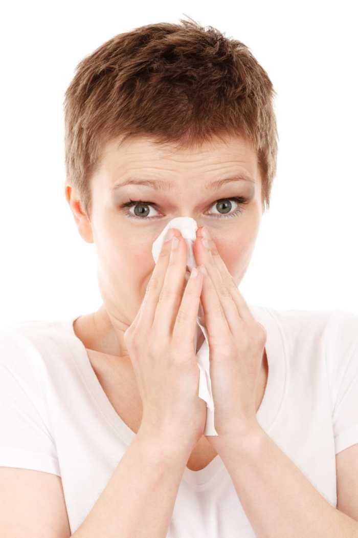 person blowing nose sick flu