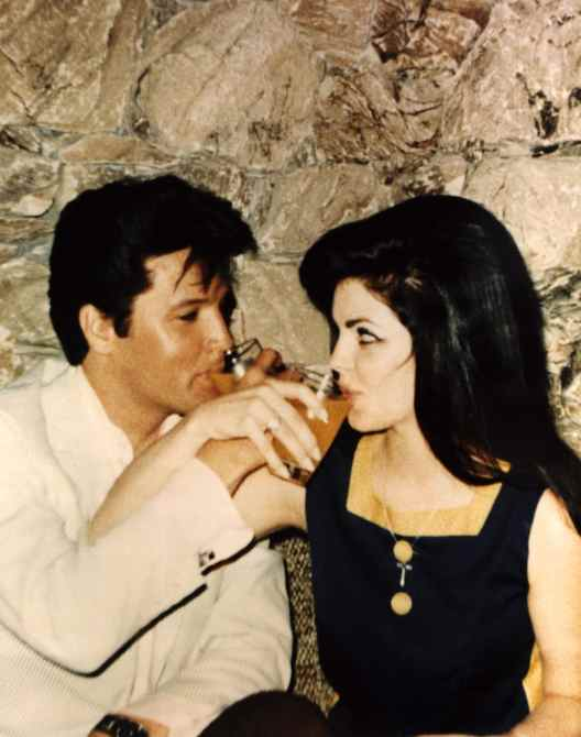 Newlyweds ELVIS PRESLEY and PRISCILLA PRESLEY toast each other after the ceremony, 1967