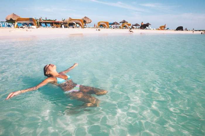 woman tanning soaking up the sun in the water on vacation