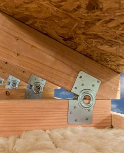 A hinged roof connector helps modular builders construct stick-frame roofs in the factory that will fold flat during shipping.