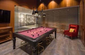 Bacardi's North American headquarters office in Miami features a custom pool table the design team envisioned, which features the brand logo and signature color in the fabric. The space also includes a display case completely custom-made by a millworker.