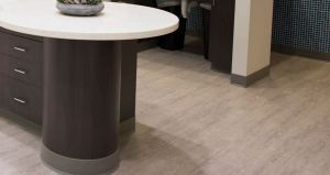 Installers lay nearly 5,000 square feet of Oak luxury vinyl plank flooring throughout the old warehouse building space, including the open areas filled with dental chairs, in private exam rooms, shared office space, corridors, and common spaces for lab sterilization.