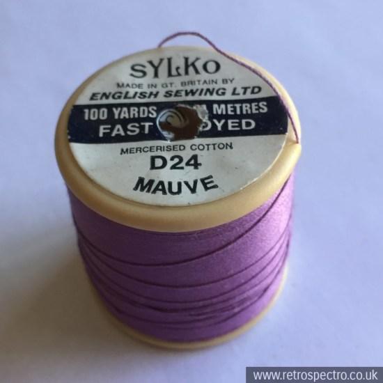A vintage plastic Dewhurst's Sylko cotton reel in D24 Mauve