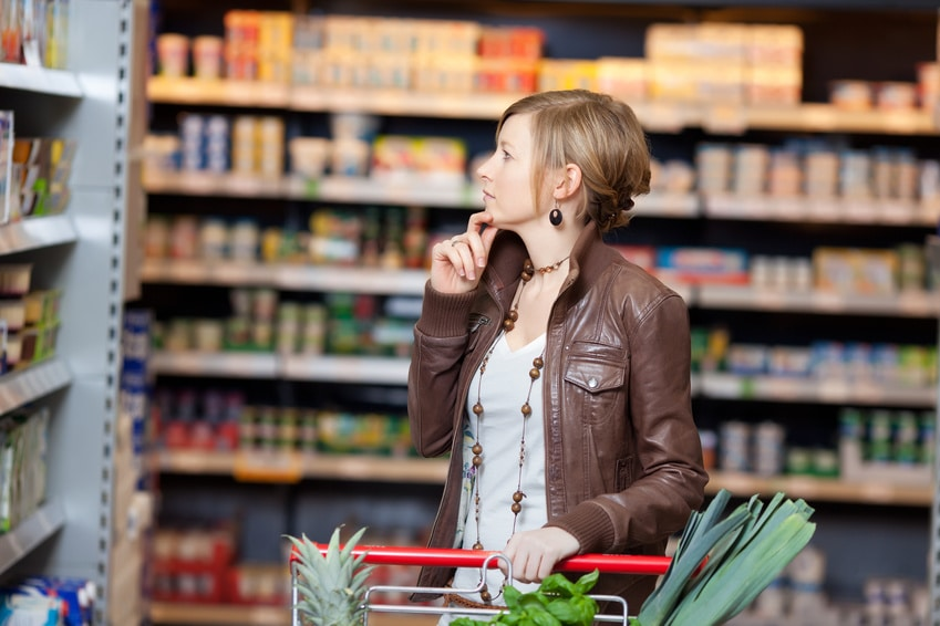 nachdenklich frau steht im supermarkt