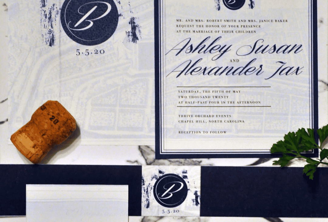 navy and white classic elegance invitation with monogram and map print by revelry + heart