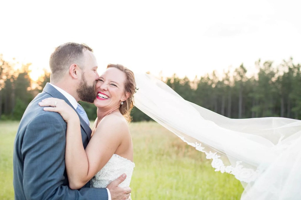 groom kisses his bride in a sunny meadow as veil gently flutters in the breeze