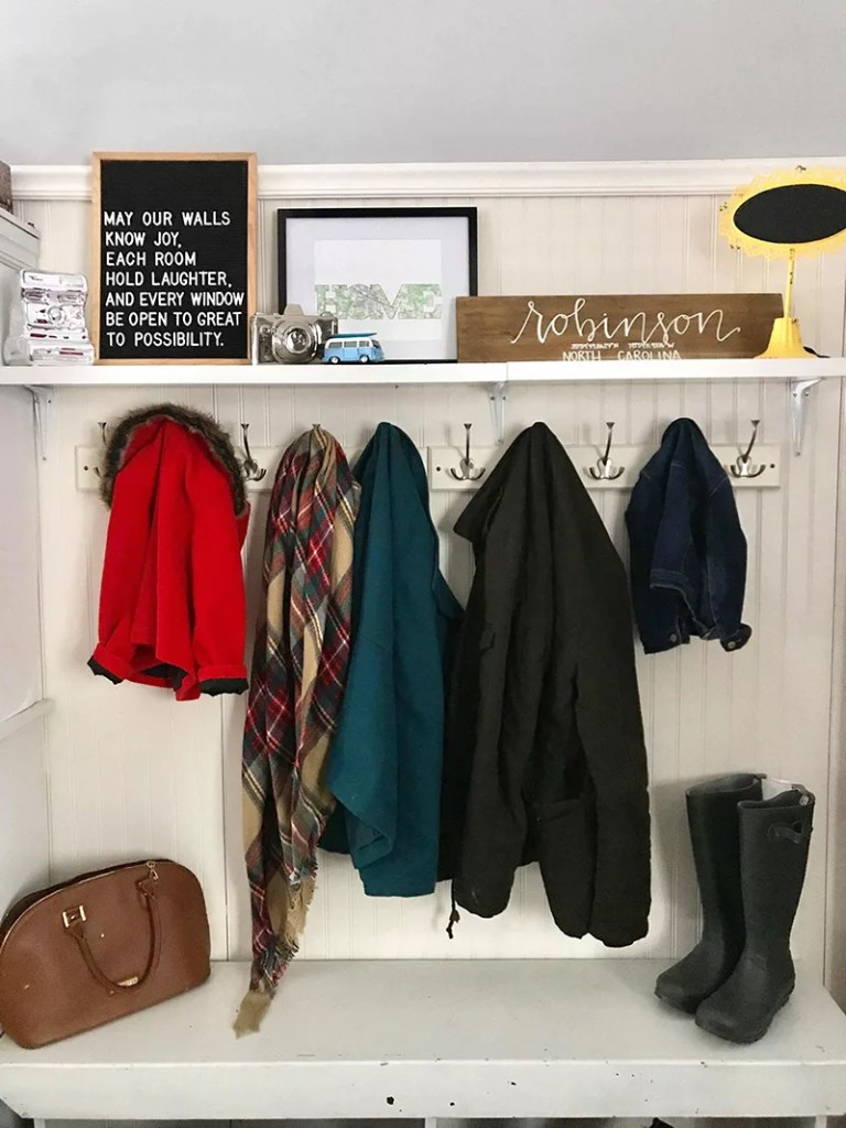 Map print in a drop zone surrounded by other family mementos, coats and entryway signage