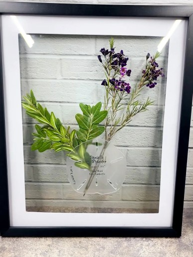 pressed wildflowers and succulent branch surround sand dollar shape art piece in home decor