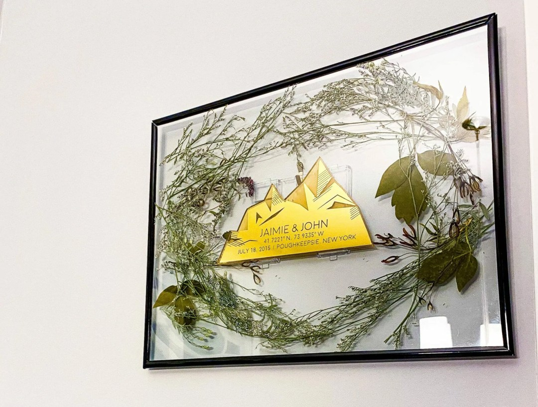 gold mirrored engraving is surrounded by delicate greenery in floating frame