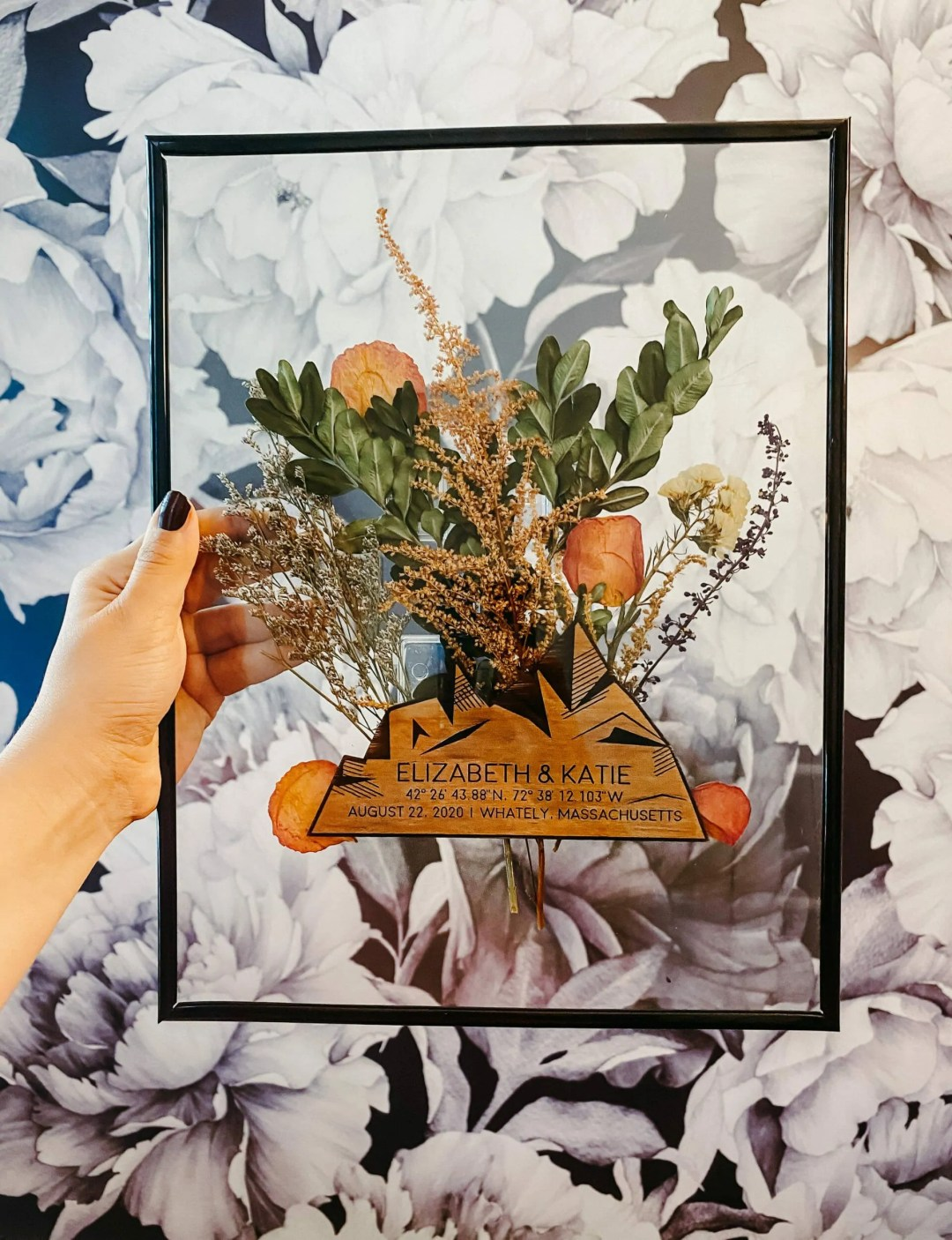 completed floating frame features wood wedding engraving and a bouquet of pressed flowers