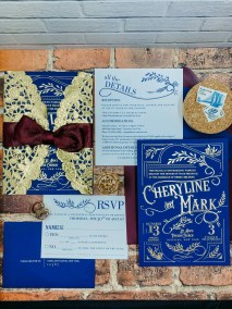 navy blue wedding invitation with gold foil imprinting - features vintage inspired design with ornate embellishments and typography. Invitation is wrapped in gold doily.