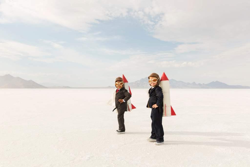 Kinder im Anzug mit einer Rakete auf dem Rücken auf dem Weg zu Innovationen