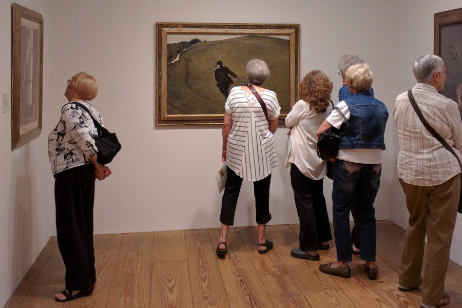 Visitors examining Andrew Wyeth's Winter.